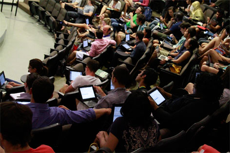 students sitting and taking notes in a lecture hall