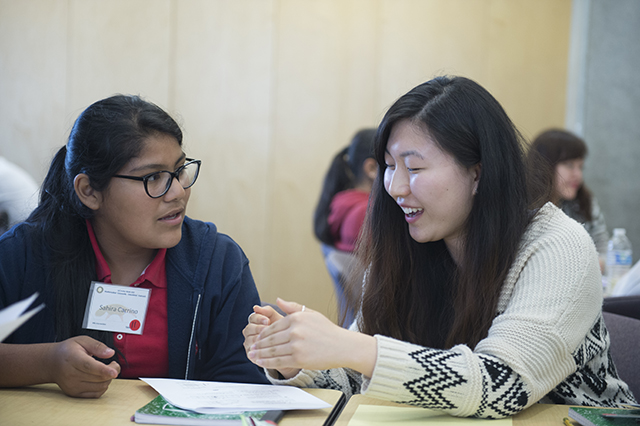 two female students talking with each other at a table